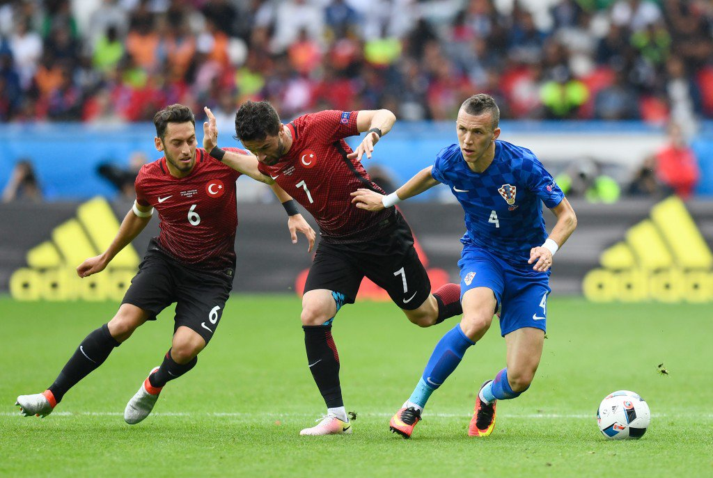 PARIS, FRANCE - JUNE 12: Ivan Perisic (R) of Croatia competes for the ball against Hakan Calhanoglu (C) and Hakan Calhanoglu (L) of Turkey during the UEFA EURO 2016 Group D match between Turkey and Croatia at Parc des Princes on June 12, 2016 in Paris, France. (Photo by Mike Hewitt/Getty Images)