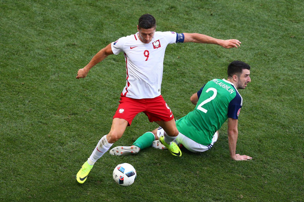 NICE, FRANCE - JUNE 12: Robert Lewandowski of Poland and Conor McLaughlin of Northern Ireland compete for the ball during the UEFA EURO 2016 Group C match between Poland and Northern Ireland at Allianz Riviera Stadium on June 12, 2016 in Nice, France. (Photo by Alex Livesey/Getty Images)