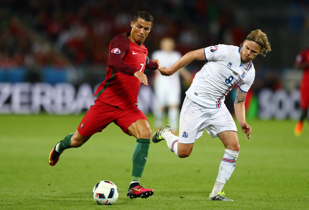 SAINT-ETIENNE, FRANCE - JUNE 14: Cristiano Ronaldo of Portugal and Birkir Bjarnason of Iceland compete for the ball during the UEFA EURO 2016 Group F match between Portugal and Iceland at Stade Geoffroy-Guichard on June 14, 2016 in Saint-Etienne, France. (Photo by Julian Finney/Getty Images)