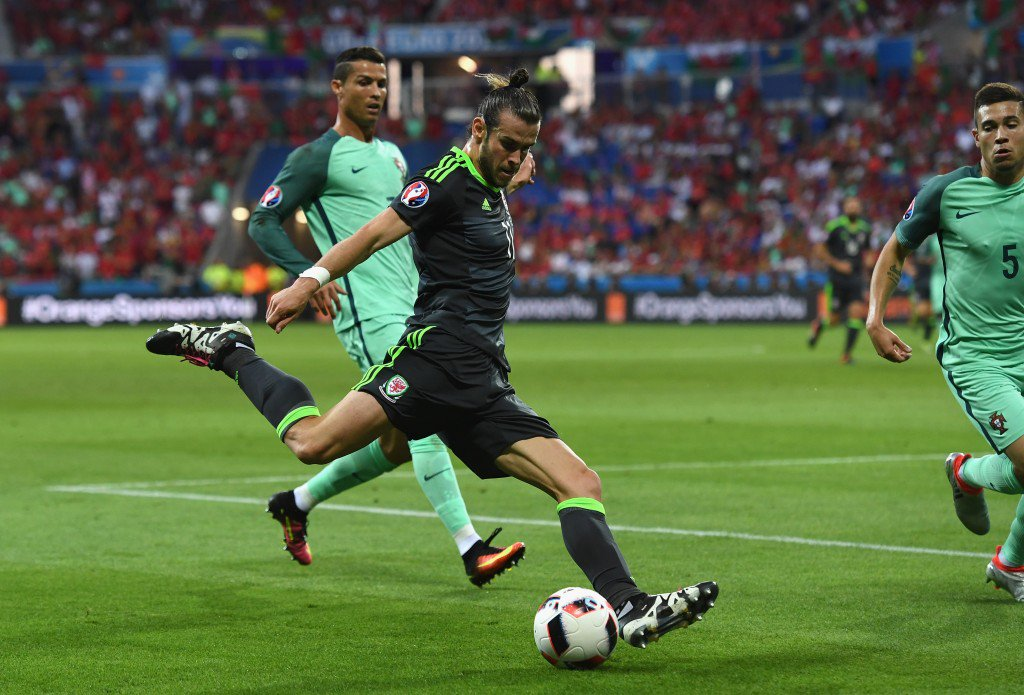 LYON, FRANCE - JULY 06: Gareth Bale of Wales crosses the ball under pressure from Cristiano Ronaldo of Portugal during the UEFA EURO 2016 semi final match between Portugal and Wales at Stade des Lumieres on July 6, 2016 in Lyon, France. (Photo by Stu Forster/Getty Images)