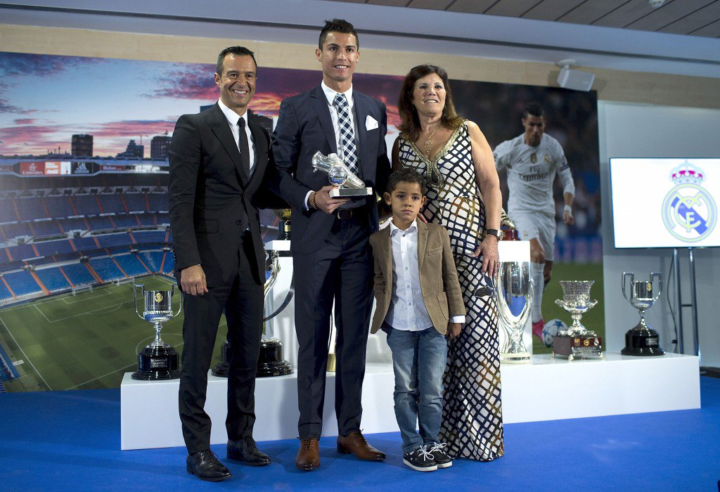 MADRID, SPAIN - OCTOBER 02: Cristiano Ronaldo (2ndL) poses for a picture with his trophy as all-time top scorer of of Real Madrid CF with his son Cristiano Ronald JR, mother Maria Dolores dos Santos and his manager Jorge Mendes (L) at Honour box-seat of Santiago Bernabeu Stadium on October 2, 2015 in Madrid, Spain. Portuguese palyer Cristiano Ronaldo overtook on his last UEFA Champions League match against Malmo FF Raul