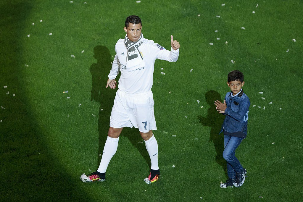 MADRID, SPAIN - MAY 29: Cristiano Ronaldo (L) of Real Madrid CF acknowledges the audience with his son Cristiano Ronaldo Jr. (R) during the celebration with their fans at Santiago Bernabeu Stadium the day after winning the UEFA Champions League Final match against Club Atletico de Madrid on May 29, 2016 in Madrid, Spain. Real Madrid CF is the only European football team with 11 European Cups (Photo by Gonzalo Arroyo Moreno/Getty Images)