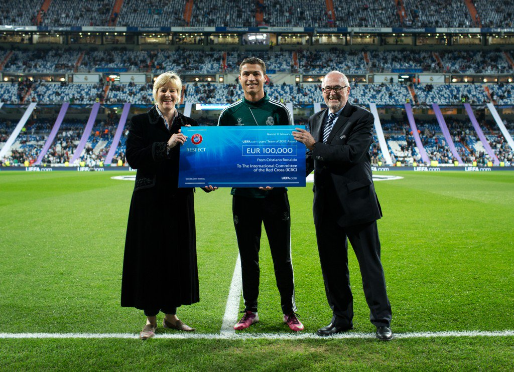 MADRID, SPAIN - FEBRUARY 13: Cristiano Ronaldo (C) of Real Madrid holds a 100,000 Euro UEFA charity cheque standing in between Peter Gillieron (R), member of the UEFA Executive Committee, and Caroline Welch-Ballentine, HR director for the ICRC, prior to the UEFA Champions League Round of 16 first leg match between Real Madrid and Manchester United at Estadio Santiago Bernabeu on February 13, 2013 in Madrid, Spain. (Photo by Jasper Juinen/Getty Images)