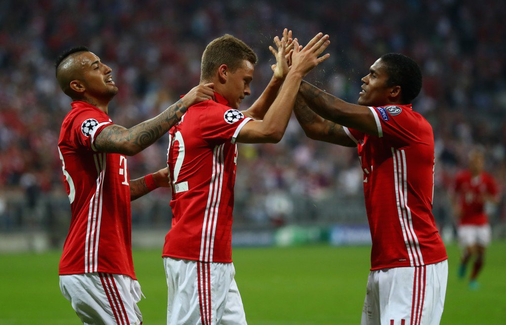 MUNICH, GERMANY - SEPTEMBER 13: Joshua Kimmich of Bayern Muenchen celebrates scoring his sides third goal wih team mates, Douglas Costa and Arturo Vidal during the UEFA Champions League Group D match between FC Bayern Muenchen and FC Rostov at Allianz Arena on September 13, 2016 in Munich, Germany. (Photo by Alexander Hassenstein/Bongarts/Getty Images)