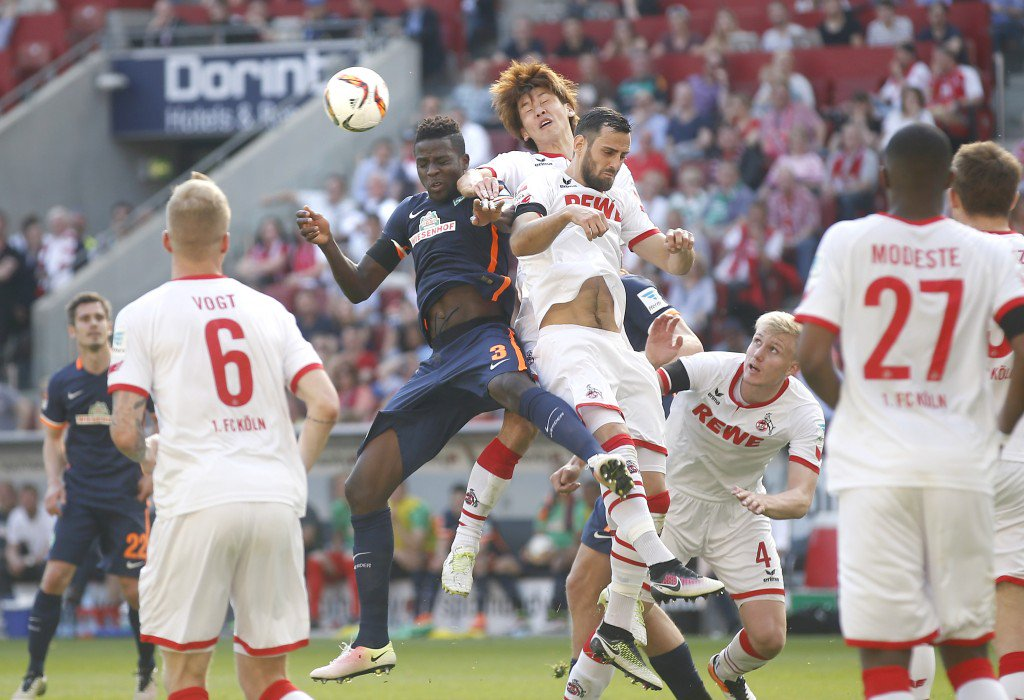 COLOGNE, GERMANY - MAY 07: Papy Djilobodji of Bremen (L) jumps for a header against Yuya Osako of Cologne (M) during the Bundesliga match between 1. FC Koeln and Werder Bremen at RheinEnergieStadion on May 7, 2016 in Cologne, Germany. (Photo by Mika Volkmann/Bongarts/Getty Images)