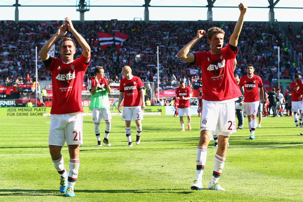 INGOLSTADT, GERMANY - MAY 07: Philipp Lahm (L), Thomas Mueller and team mates of Muenchen celebrate being Bundesliga champions after beating Ingolstadt 2-1 in Rafinha (front) and team mates of Muenchen celebrate their team's fourth consequtive German Championship after the Bundesliga match between FC Imgolstadt and FC Bayern Muenchen at Audi Sportpark on May 07, 2016 in Ingolstadt, Bavaria.