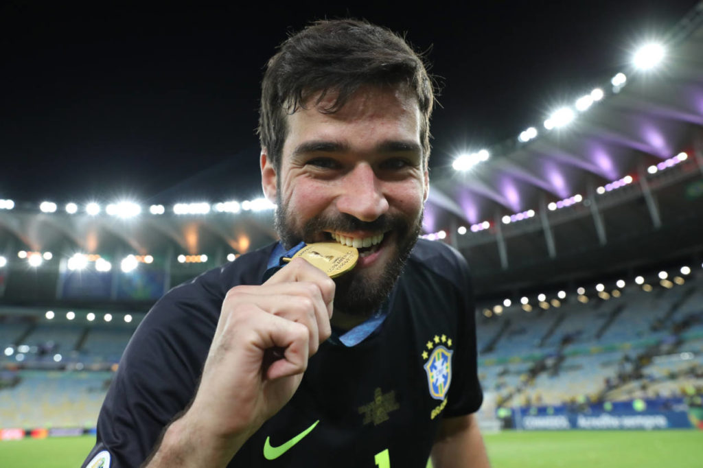 RIO DE JANEIRO, BRAZIL - JULY 07: Alisson Becker of Brazil bites his champion medal after winning the Copa America Brazil 2019 Final match between Brazil and Peru at Maracana Stadium on July 07, 2019 in Rio de Janeiro, Brazil.