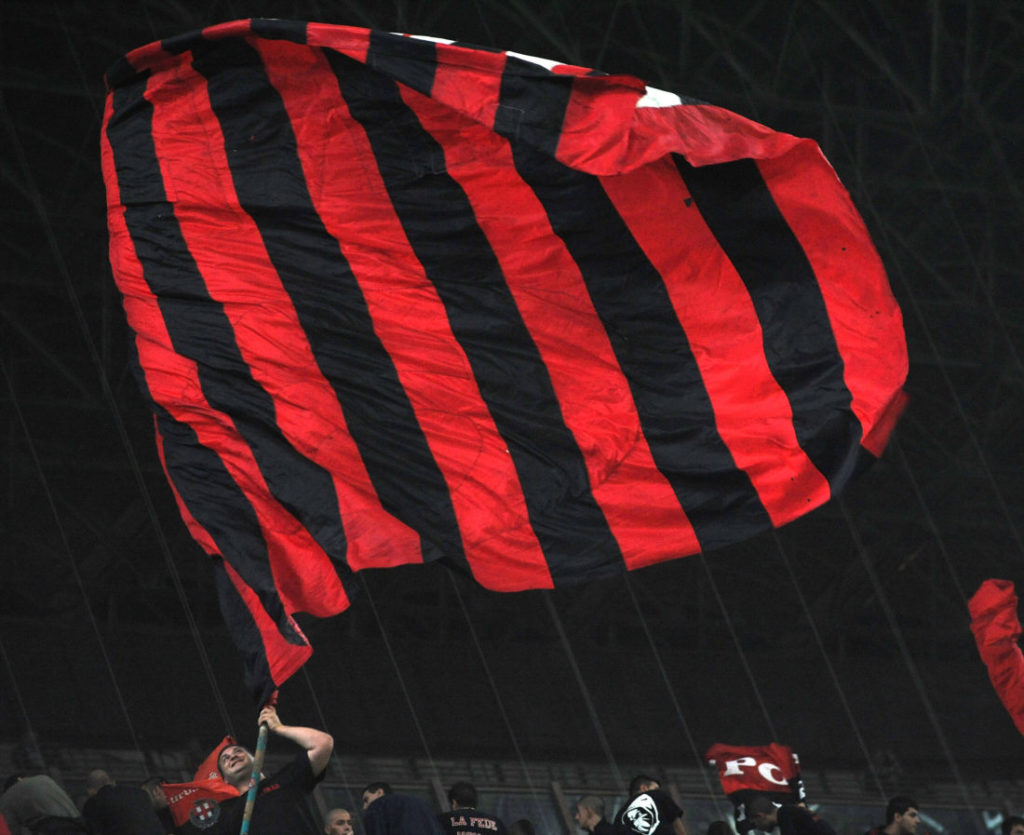 MILAN, ITALY - SEPTEMBER 27: A fan of AC Milan waves his flag during the Serie A match between AC Milan and AS Bari at Stadio Giuseppe Meazza on September 27, 2009 in Milan, Italy.