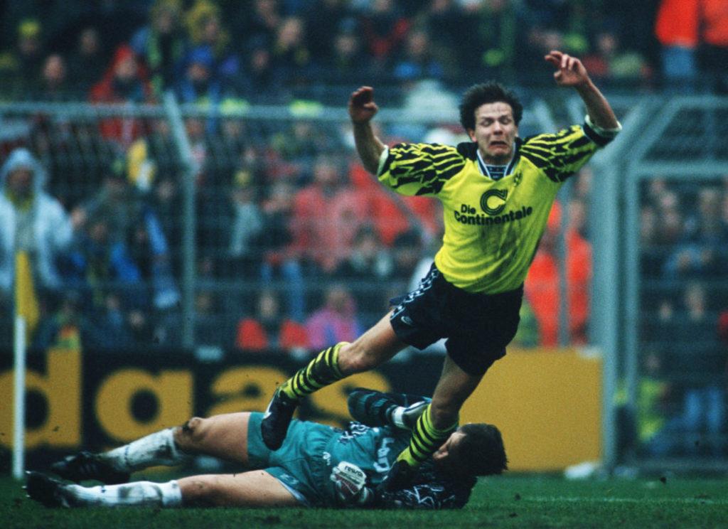 DORTMUND, GERMANY - MAY 3: Goalkeeper Bernd Dreher of Uerdingen and Andreas Moeller (R) of Dortmund battle for the ball during the bundesliga match between Borussia Dortmund and KFC Uerdingen 05 on May 3, 1996 in Dortmund, Germany.