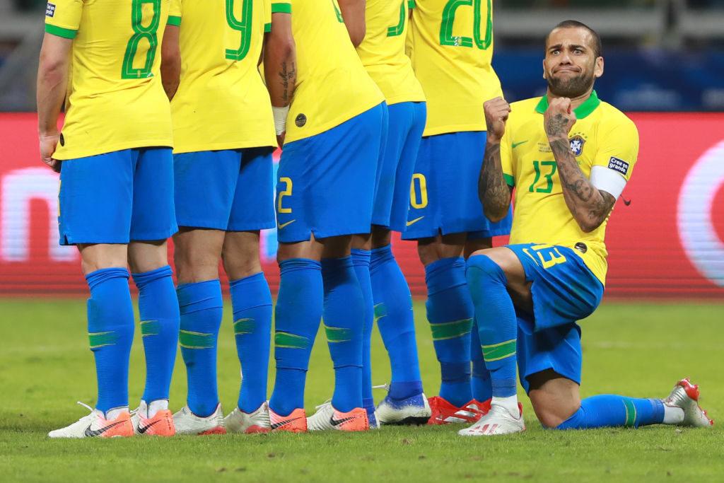 Kann man mal so machen: Brasiliens Kapitän Dani Alves freut sich über einen verschossenen Freistoß von Lionel Messi....