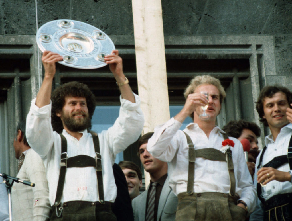 MUNICH, GERMANY - JUNE 14: Paul Breitner (L) and Karl-Heinz Rummenigge of Bayern Munich celebrates with the trophy after winning the German Championship 1981 at the guildhall on June 14, 1981 in Munich, Germany.