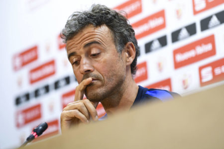 Spain head coach Luis Enrique applauds Cristiano Ronaldo and Lionel Messi as Spain prepares to take on Portugal in a friendly meeting.