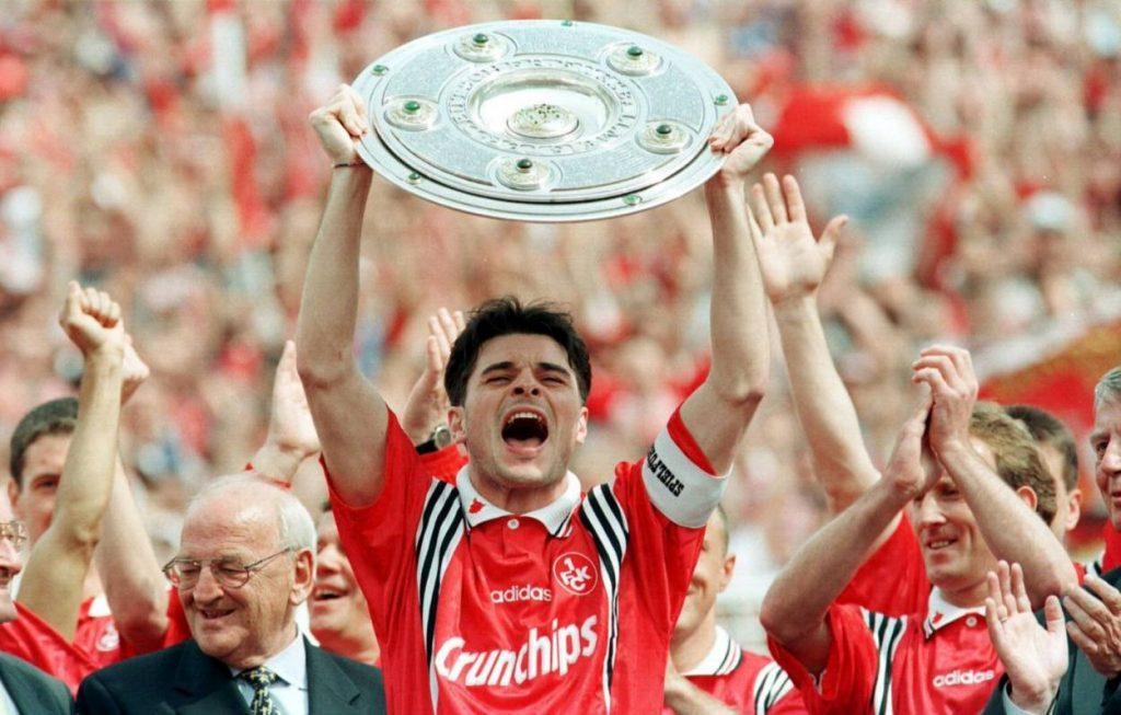 Kapitän Ciriaco Sforza nimmt die Meisterschale für den 1. FC Kaiserslautern 1998 in Empfang. Rechts: Fußball-Legende Andreas Brehme.